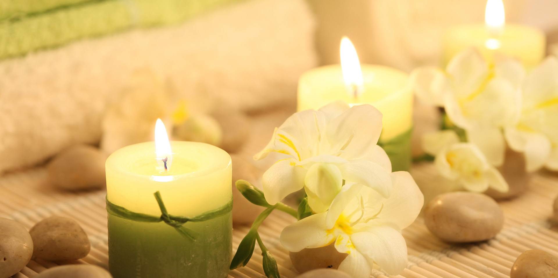 Royal Health Therapies main image: towels, flowers, and candles in soft greens, browns, and yellows