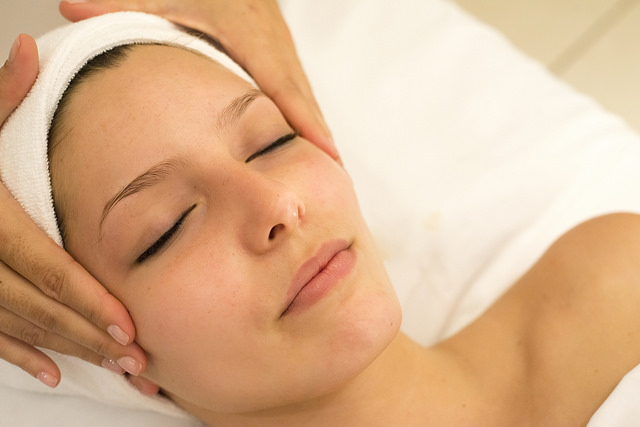 Headshot of a woman face-up, receiving a head massage such as craniosacral